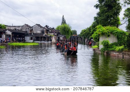 August 8 2015. Xitang Water Town China. Tourists on boats navigating the water canals of Xitang ancient town in jiashan county zhejiang province china.