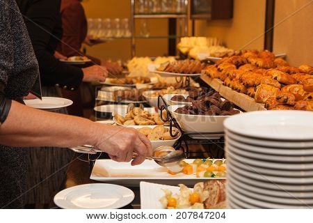The people at the party eat sweets and cakes. All kinds of snacks. Coffee break with sweet snacks - muffins, cookies, cheesecakes, muffins