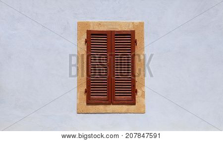 closed window with brown shutters on blue ancient wall in small town, Italy.