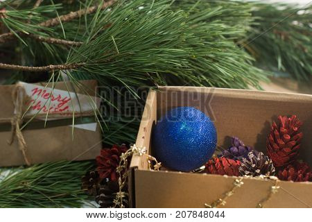 Festive box with decoration on Christmas tree. Colorful strobilas and blue ornament ball gathering in carton, wrapped present with greeting memo nearby. New Year family traditions and decor concept