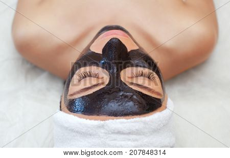 The Procedure For Applying A Black Mask To The Face Of A Beautiful Woman. Spa Treatments And Care Of