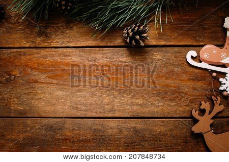 Christmas and New Year holiday background. Close up handmade ornaments of skate and deer on right and pine with strobila above on wooden table, festive decoration concept. Free space in the middle