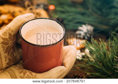 Warm Christmas holiday with latte and cookies. Close up unrecognizable woman holding cup of drink in knitted gloves hands on festive background. Cozy xmas evening on festival and fairs concept