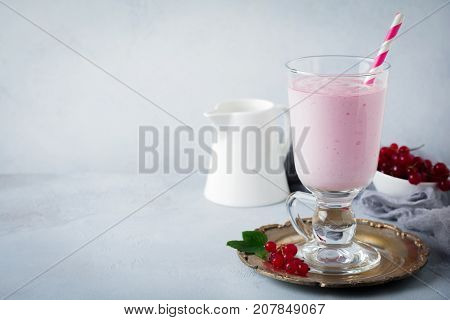 Red currant yoghurt smoothies milkshake in a glass cup on a gray concrete background. Selective focus. Copy space.
