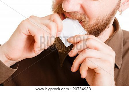 Young bearded man in brown shirt holds a contraceptive in mouth in photo studio isolated on a white background. Close-up of contraceptive.