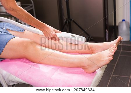 Hair removal cosmetology procedure from a therapist at cosmetic beauty spa clinic. Laser epilation and cosmetology