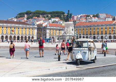 White Tuk Tuk Taxi Cab Stands In Lisbon