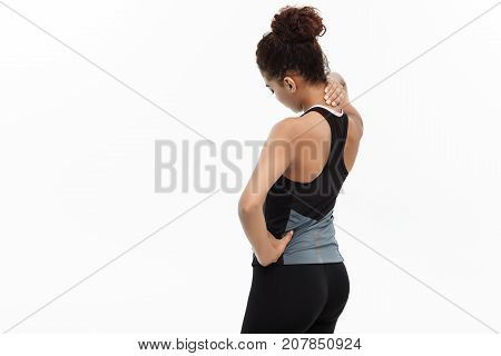 Healthy and Fitness concept - portrait of African American girl suffers a muscle injury standing holding her neck and lower back with back view. Isolated on white background.