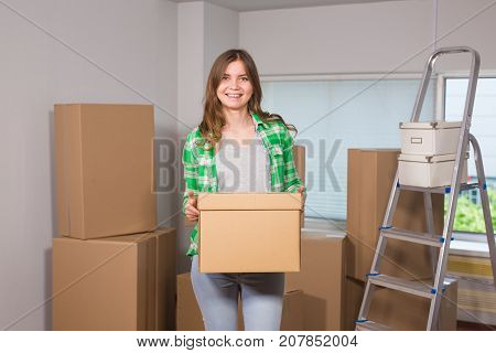 Beautiful young woman holding a cardboard box. Ready for moving. Moving in a new apartment