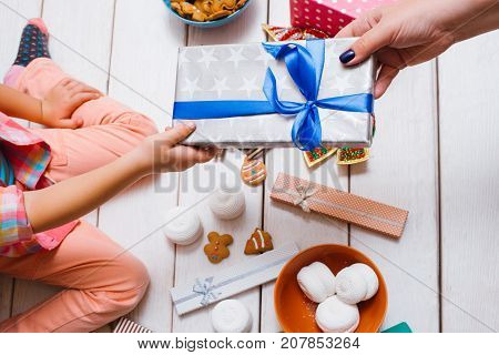 Christmas miracle. Family love on New Year's day. Unrecognizable women together on wooden background top view. Dream gift giving. Favorite time, festive decorations