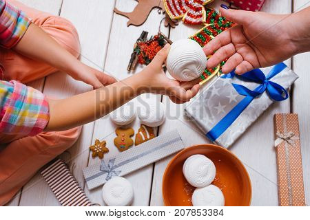 Family love. Christmas festive food. Favorite time of year, unrecognizable females with tasty sweets on wooden background. Yummy presents top view