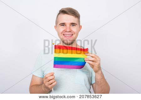 Fun male standing with hand holding the rainbow flag. Concept of sexual minority and LGBT.