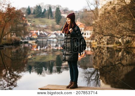 A tourist girl with a backpack standing on the shore and enjoying the nature and views of the city of Cesky Krumlov in the Czech Republic. One of the most beautiful small towns in the world. Europe. The concept of solo travel.