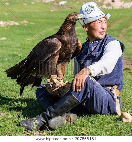 Eagle Hunter Holds His Eagles, Sitting On The Ground