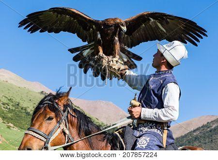 Eagle Hunter Holds His Eagles On Horseback