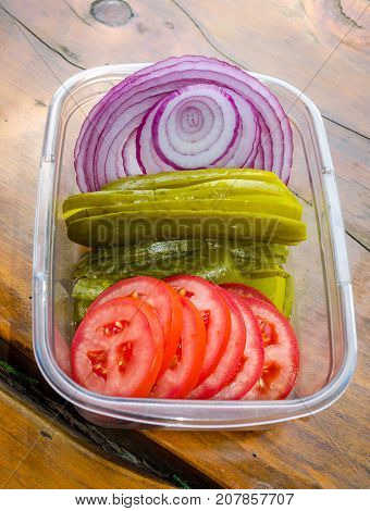 Fresh sliced onion, pickle and tomato.  Healthy vegetable toppings for a hamburger. Perfect addition to a picnic, tailgate, party of tasty meal.