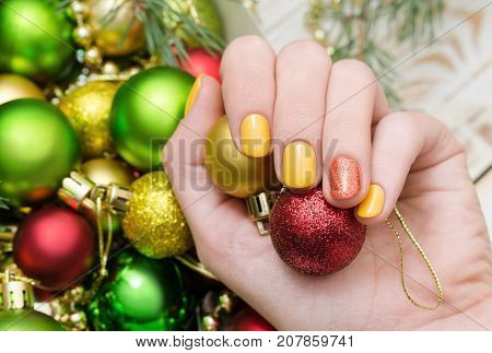 Beautiful female hand with yellow nail design. Christmas manicure with glitter accent.