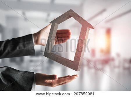 Business woman in black suit keeping stone house symbol in hands with sunlight and office view on background. Mixed media.