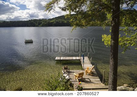 Private dock, chairs and swimming area on Squam Lake in New Hampshire. A loon swims near the dock.