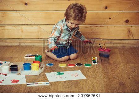 Boy Painter Painting On Wooden Floor