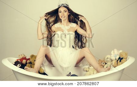 Woman with long hair white dress and crown. Girl sitting on bath tub on grey background. Beauty salon and wedding fashion. bath with toy bear and girl in white dress. Hairdresser and spa relax.