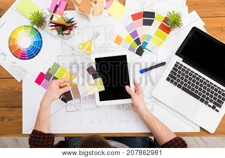Interior designer working with color palette top view. Architect choosing colors for building decoration with digital tablet with blank screen, mockup