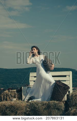 Girl in white dress posing on blue sky. Summer vacation holidays and celebration. Winery tour concept. Woman with glass of wine wicker bottle and basket. Model with alcohol drink on sunny day.