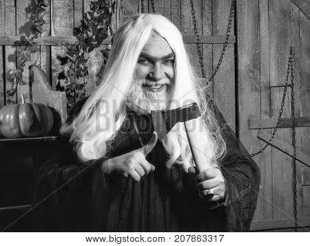 Old grey-haired sorcerer in black robe with demonic smile hold axe near finger in wooden house