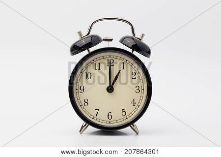 black alarm clock on white background, one o'clock