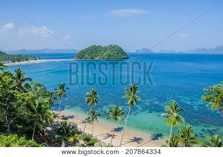 Tropical Beach with Palm trees. Many Islands in ocean in Background, El Nido, Palawan, Philippines.