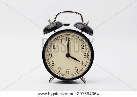 black alarm clock on white background, four o'clock