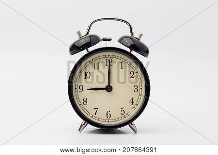 black alarm clock on white background, nine o'clock