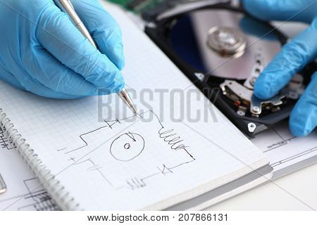 A male repairman in blue protective gloves examines an electrical printer's schematic of the hard disk unit that performs its diagnostics and repair