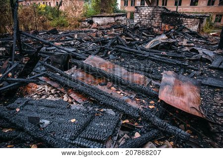 Burned house, ruins of destroyed building by fire, ash and coal, arson concept