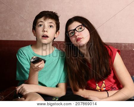 Teenage Kids Siblings Boy And Girl Watch Tv  Movie With Remote Control