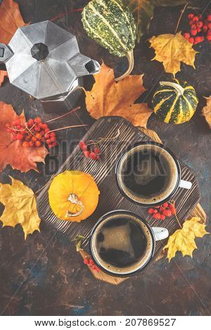 Autumn still life with enamel cups with coffee pumpkins and maple leaves. Top view. Top view