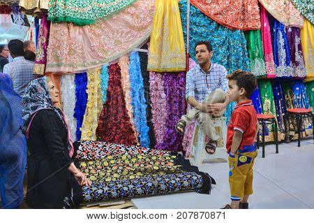 Fars Province Shiraz Iran - 19 april 2017: Department of tissues in the central bazaar shoppers inspect goods the seller is bored sitting on a chair.