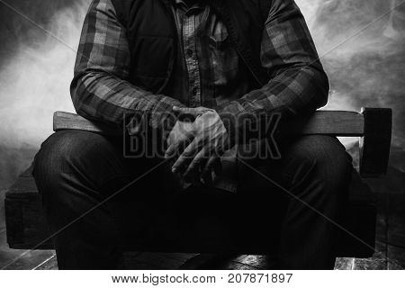 Armed axeman in atmospheric smoke. Dangerous male. Unrecognizable rural man with axe in focus on foreground closeup, spooky atmosphere, danger concept