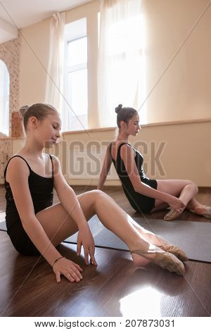 Young ballerinas exercises. Teenage sport. Pensive ladies in dance class, pretty girls stretching. Sensibility from childhood. Gym background, healthy teen lifestyle, femininity concept