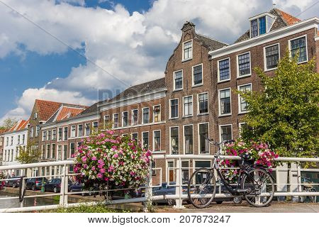 LEIDEN, NETHERLANDS - SEPTEMBER 03, 2017: Flowers and bicycle on a bridge over a historic canal in Leiden Holland