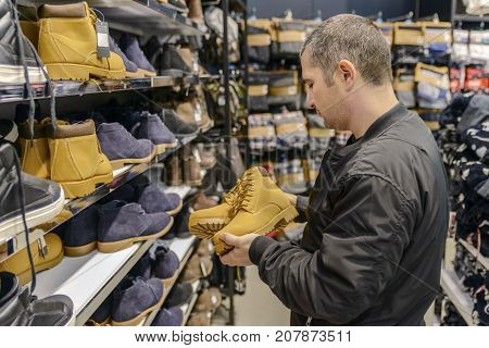 young man with short hair chooses his shoes with a good mood (выбирает Botinki )