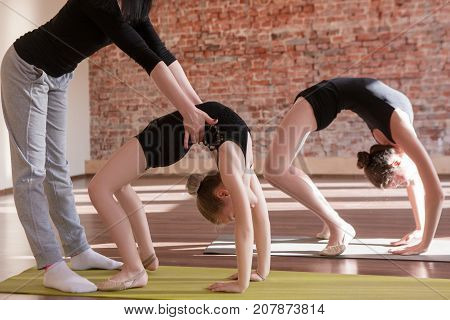 Ballerinas workout. Teenage sport life. Girls rhythmic gymnastics in focus on foreground with female coach. Gym background, healthy teen lifestyle, exercise concept