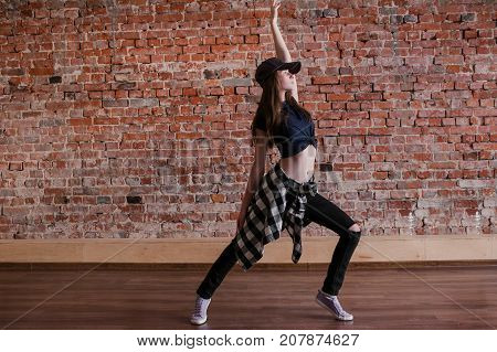 Dance is life. Hip hop lifestyle. Happiness in moving, sporty teenage girl on brick wall background with free space. Flexible dancing young female, breakdance concept