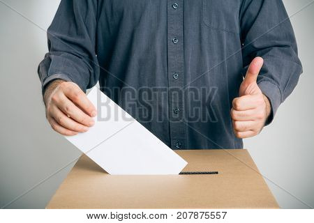man casting his vote, holding thumb up