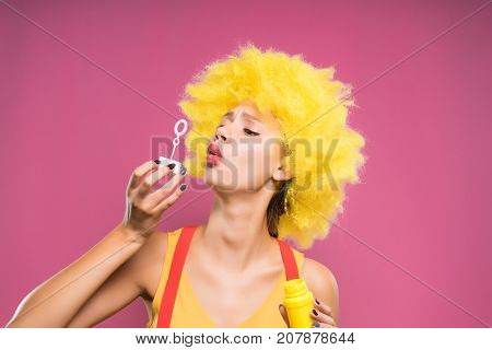 funny girl in a bright yellow wig blowing soap bubbles