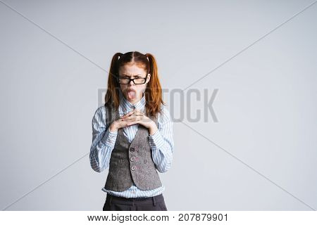 girl with two tails in glasses shows tongue and looks directly into camera