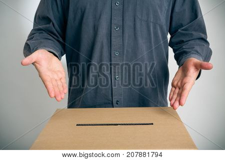 man pointing at ballot box, inviting you to cast your vote