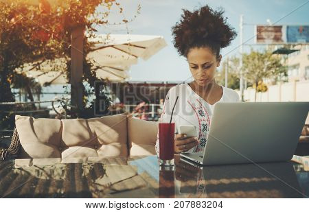 Serious young black female freelancer answering incoming phone message while sitting in street bar or cafe and working on project using laptop with copy space place for logo your text or advertising