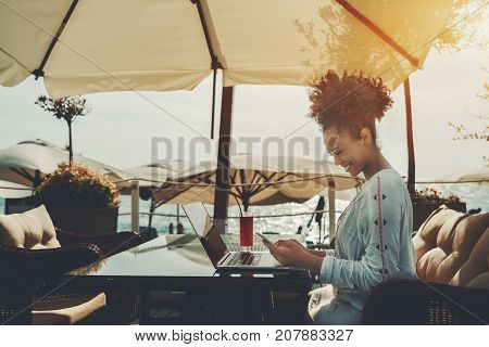 Cheerful young black curly female is working alone with her documents using laptop in cafe nearshore on a sunny summer day and laughing on a text of incoming message in her mobile phone