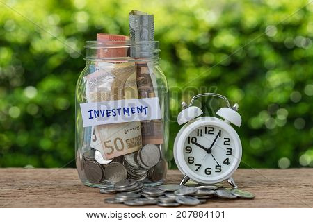glass jar bottle labeled as investment with full of coins and banknotes white alarm clock as savings or investment concept.